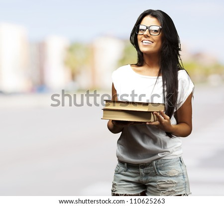 portrait of young girl holding books at crowded city