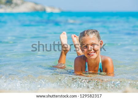 Portrait of young girl swimming in the transparent sea