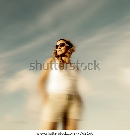 Portrait of young girl wearing sunglasses standing against blue summer sky
