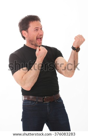 Portrait of young handsome charismatic man in black shirt screaming with hands up