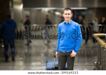 Portrait of young happy handsome travelling man wearing smart casual style clothes walking in modern airport. Cheerful guy travelling with suitcase. Copy space
