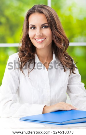 Portrait of young happy smiling business woman working with documents at office