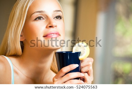 Portrait of young happy smiling woman with teapot and cup, indoors. Caucasian blond model in home leisure and happiness concept.