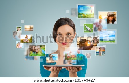 Portrait of young happy woman sharing her photo and video files in social media resources using her modern tablet computer