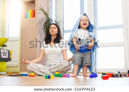 Portrait of young happy yoga mom spending time with her little baby boy, meditating in lotus position while her kid son playing games at home.