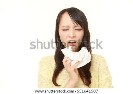 portrait of young Japanese woman with an allergy sneezing into tissue on white background