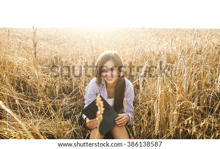 Portrait of young latin hispanic girl sitting on golden reap wheat in yellow sunset field reading black book on summer nature background Woman with long brunette hair laugh and looking at paper page