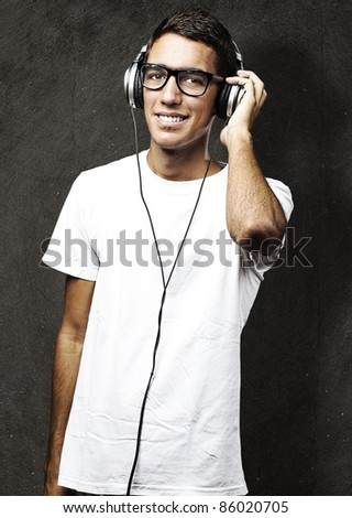 portrait of young man listening to music against a grunge wall