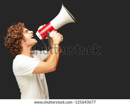 Portrait Of Young Man Shouting With A Megaphone Isolated On Black Background