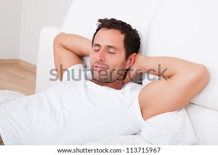 Portrait Of Young Man Sleeping On Bed In Bedroom