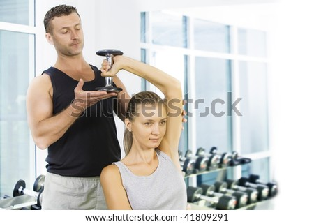 Portrait of young nice couple getting busy in gym