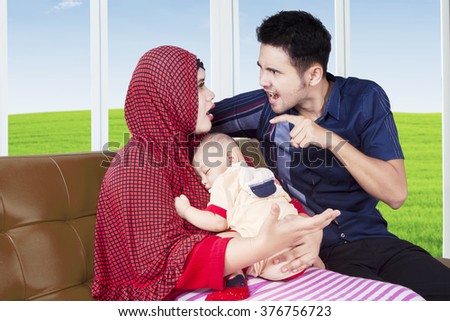 Portrait of young parents arguing at home while sitting on sofa and carrying their baby