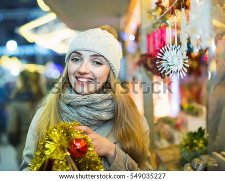 Portrait of young positive cheerful happy woman at Christmas fair  in evening