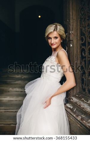 Portrait of young pretty bride in long dress standing in front of the old door