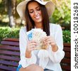 Portrait of young pretty woman sitting on bench at summer or autumn park and daydreaming while holding money and looking up to the sky. Wearing stylish clothes - straw hat and white blouse - stock photo