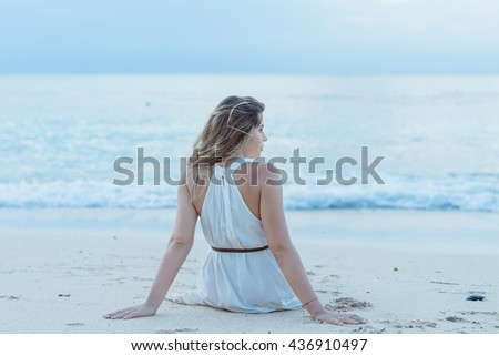 Portrait of young pretty woman sitting on the Beach.Woman sitting on the beach turned wistfully looking at the sky.girl on the beach watching the sunset.Bali.Indonesia Ho;iday