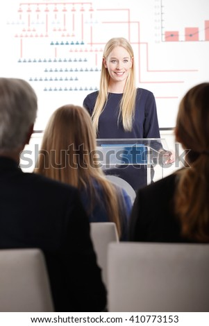 Portrait of young professional woman giving speech at business seminar.