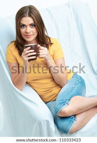 Portrait of young smiling woman sitting at sofa with coffee cup