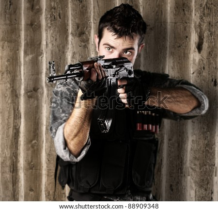 portrait of young soldier aiming with rifle against a grunge wooden wall