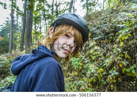 portrait of young teenage boy in forest with bike helmet