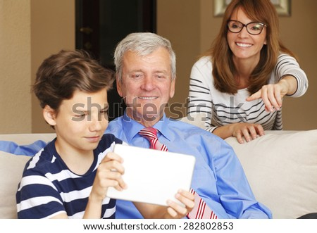 Portrait of young teenager sitting at sofa with his grandfather. Grandson holding digital tablet in his hands and taking funny self-portrait while her mother sitting behind the sofa and smiling.