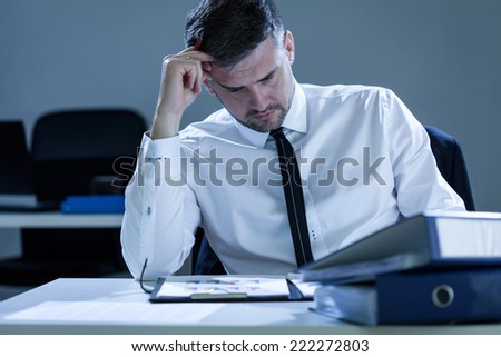 Portrait of young, tired businessman reading notes