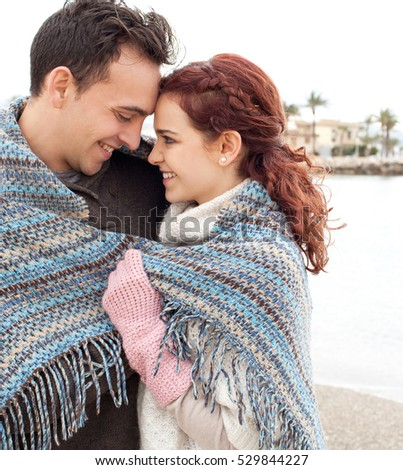 Portrait of young tourist couple hugging sharing blanket, smiling on romantic winter beach holiday, outdoors recreation. People enjoying travel destination, lifestyle, togetherness, nature exterior.
