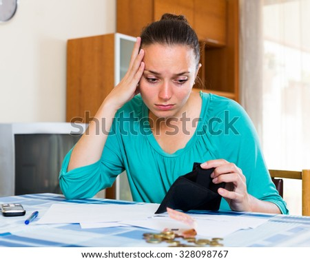 Portrait of young unhappy businesswoman with empty wallet