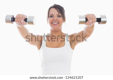Portrait of young woman exercising with dumbbells over white background