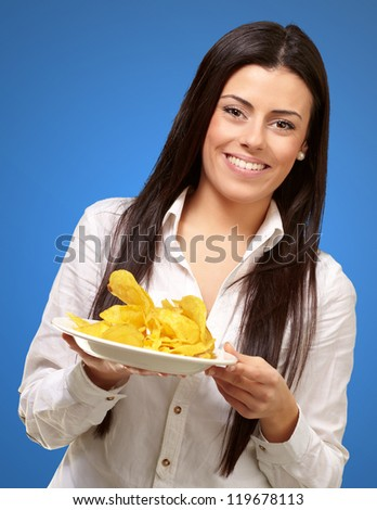 portrait of young woman holding a potato chips plate over blue background