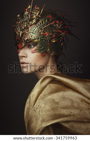 Portrait of young woman in creative head wear and gold color clothes on dark background
