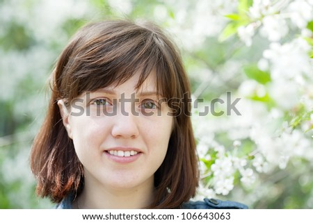 portrait of young woman in spring blossoming garden