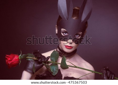 Portrait of young woman posing with rose in rabbit mask.