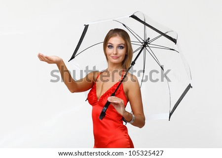 Portrait of young woman with umbrella in studio