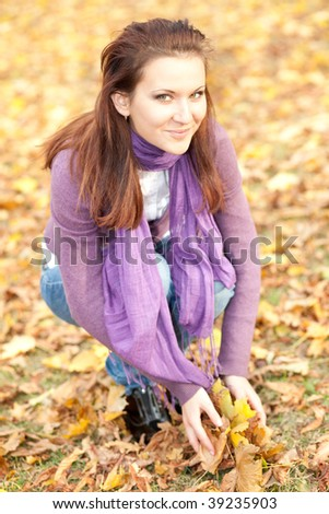 Portrait of young woman with yellow leaves in autumn park. Soft focus.