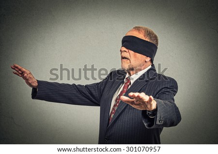 Portrait senior business man in suit blindfolded stretching his arms out isolated on gray wall background