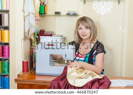 Portrait serious, concentrated charming adult woman seamstress thinking and working in studio