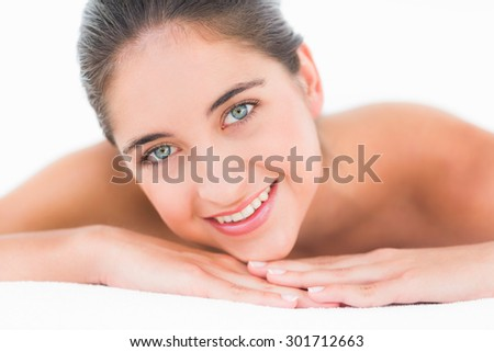 Portrait smiling pretty brunette on massage table with white backgroung
