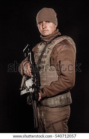 Portrait soldier or private military contractor holding rifle. war, army, weapon, technology and people concept. Image on a black background.