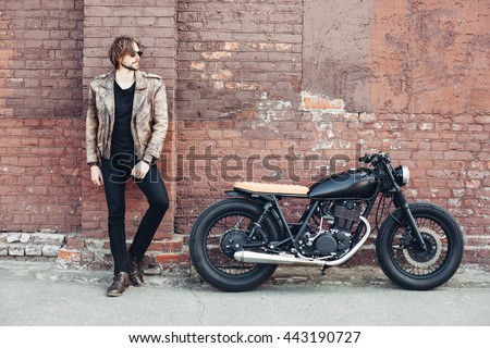 portrait young guy with a beard and mustache with sunglasses and white T-shirt posing on the street vintage man, fashion men, hipster street casual a motorcycle