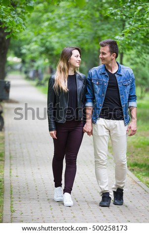 Pose of  couple taking a walk in the park and looking one at other's eyes