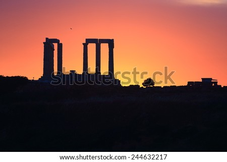 Poseidon temple surrounded by orange light on the sky at sunset, Cape Sounio, Greece