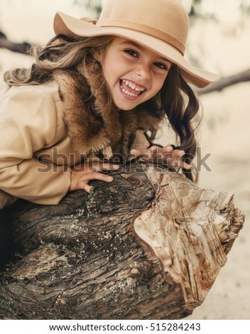 poses in the autumn forest beautiful girl with long hair in a hat and a coat with fur