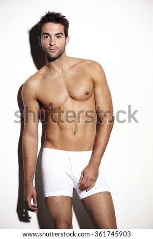 Posing young man in white shorts against white background