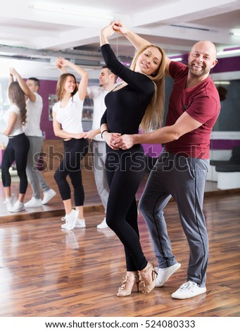 Stock Photo Positive Adult Couples Enjoying Of Partner Dance And Smiling Indoor on Foxtrot Clothing