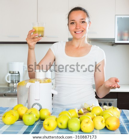 Positive adult girl making juice from apples at kitchen