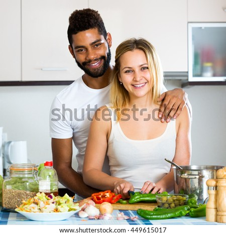 Positive black husband helping white wife preparing healthy dinner