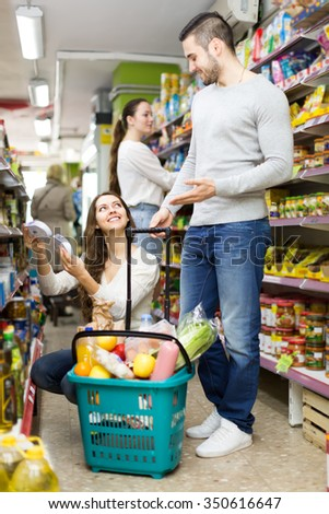 Positive couple man and woman buying groceries in a shop. Woman is holding products in her hands while man is standing near full basket of healthy food. Focus on woman