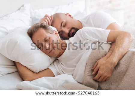 Positive delighted non-traditional couple sleeping together