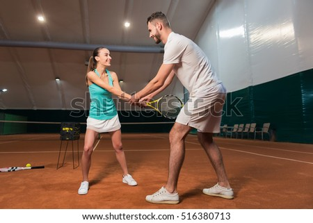 Positive friends learning to play tennis
